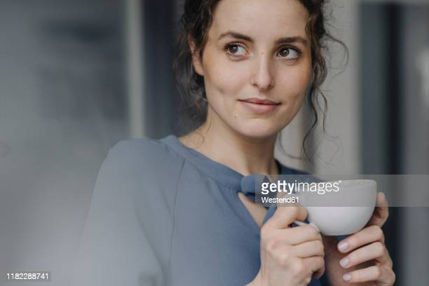 portrait of young woman relaxing with cup of coffee - kaffee getränk stock-fotos und bilder