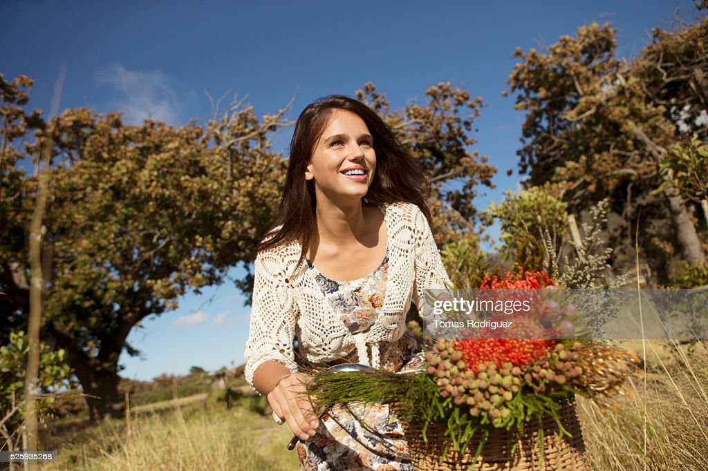 Portrait of young woman riding bicycle : Stock Photo