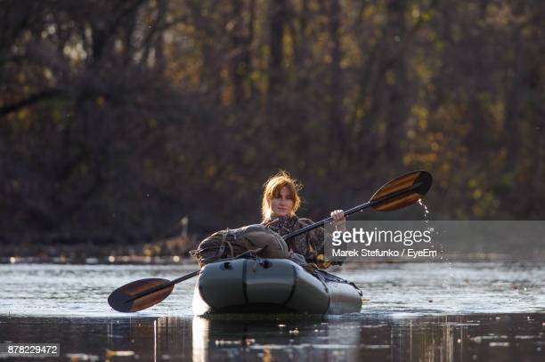 portrait of young woman sailing inflatable raft on river - marek stefunko stockfoto's en -beelden