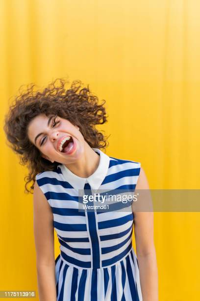 portrait of young woman shaking her head, yellow background - striped dress stock pictures, royalty-free photos & images