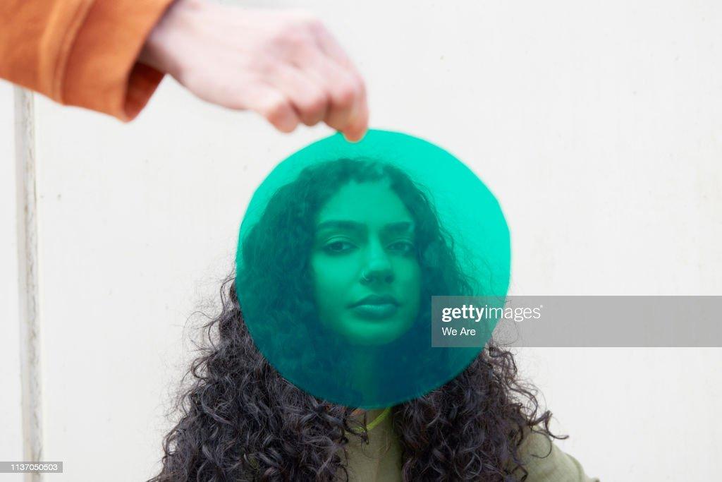 Portrait of young woman shot through green cellophane : Stock Photo