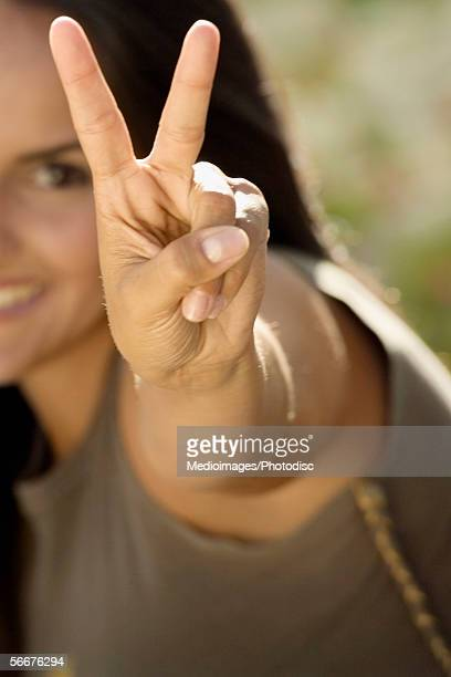 Portrait of young woman showing a peace sign