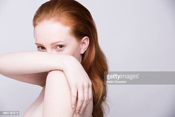 Portrait of young woman, side view, bare shoulders, looking at camera