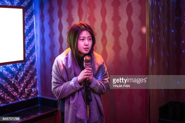 portrait of young woman singing into microphone - karaoke stock pictures, royalty-free photos & images
