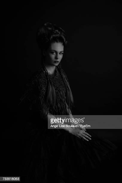 Portrait Of Young Woman Sitting Against Black Background