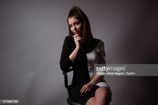 portrait of young woman sitting against gray background - bogdan negoita stock pictures, royalty-free photos & images