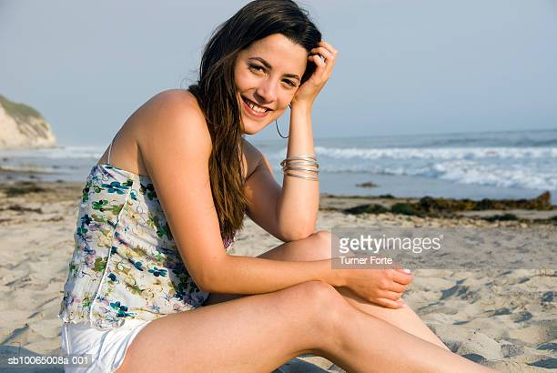 Portrait of young woman sitting at beach, smiling