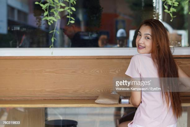 Portrait Of Young Woman Sitting At Table In Cafe