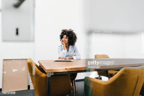 portrait of young woman sitting at table in office - hand on chin stock pictures, royalty-free photos & images