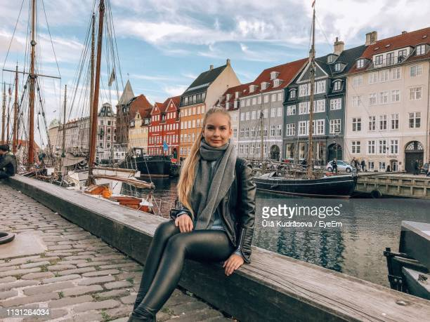 portrait of young woman sitting by canal against buildings - nyhavn stock pictures, royalty-free photos & images