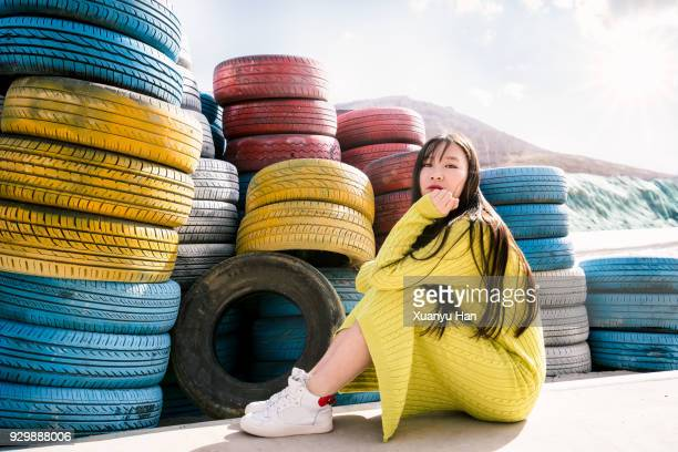 portrait of young woman sitting by the tires - long bright yellow dress stock pictures, royalty-free photos & images
