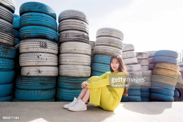 Portrait Of Young Woman Sitting by the Tires