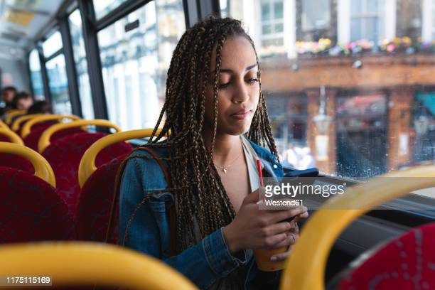 portrait of young woman sitting in bus looking at cell phone, london, uk - bus stock pictures, royalty-free photos & images