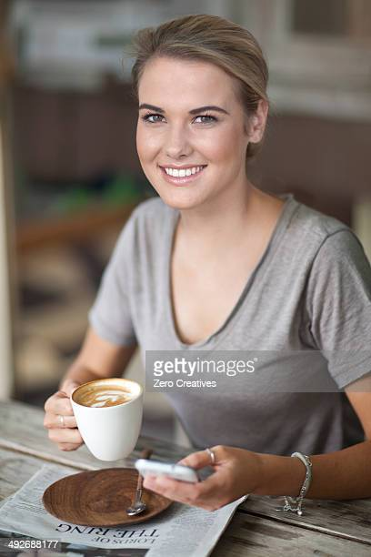 Portrait of young woman sitting in cafe with coffee cup and cellphone