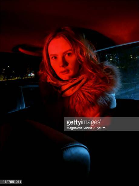 portrait of young woman sitting in car at night - red light stock pictures, royalty-free photos & images
