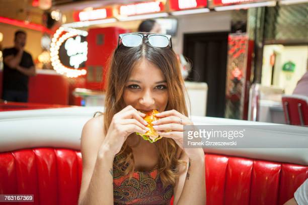 Portrait of young woman sitting in diner, eating sandwich