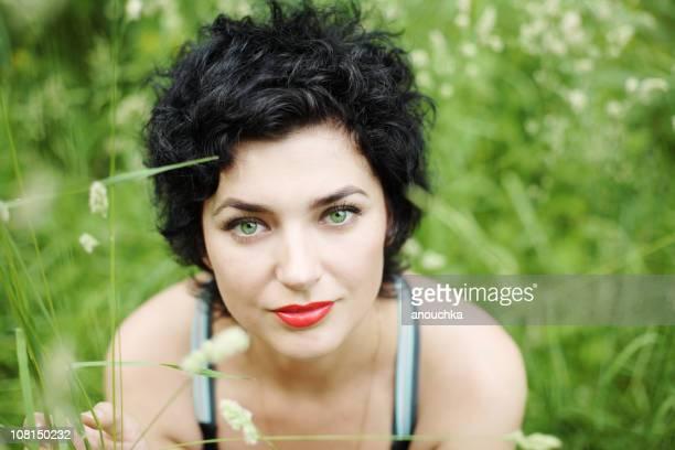 portrait of young woman sitting in grass - groene ogen stockfoto's en -beelden