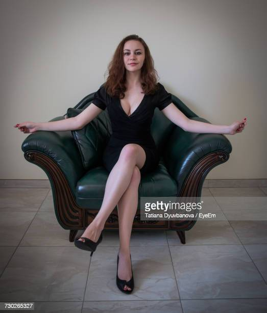 Portrait Of Young Woman Sitting On Armchair Against Wall At Home