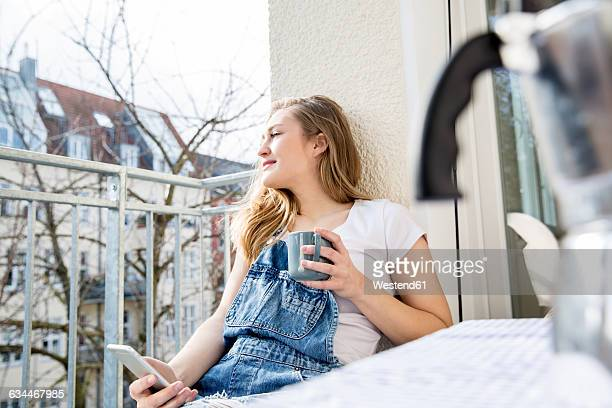 Portrait of young woman sitting on balcony with smartphone and cup of coffee