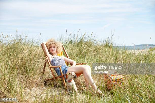 Portrait of young woman sitting on beach chair in the dunes watching something