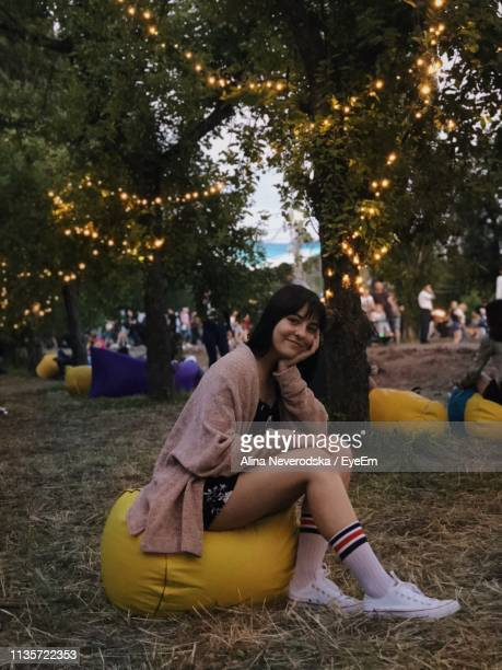 portrait of young woman sitting on bean bag over field - sacco photos et images de collection
