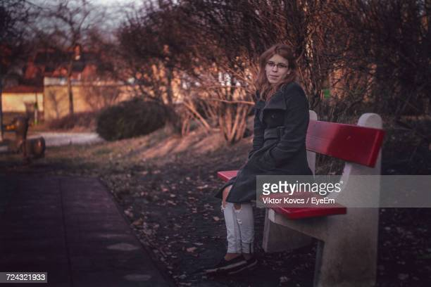 Portrait Of Young Woman Sitting On Bench By Footpath At Park