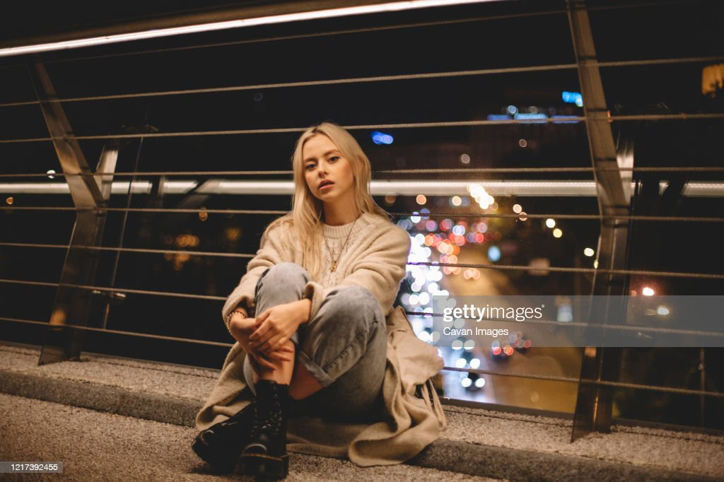 Portrait of young woman sitting on bridge in city at night : Stock Photo