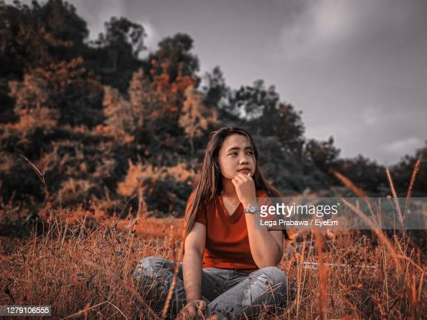 portrait of young woman sitting on field - simple living stock pictures, royalty-free photos & images