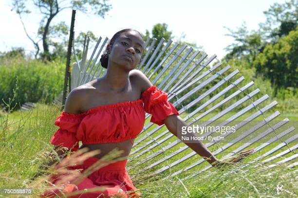 Portrait Of Young Woman Sitting On Grassy Field During Sunny Day