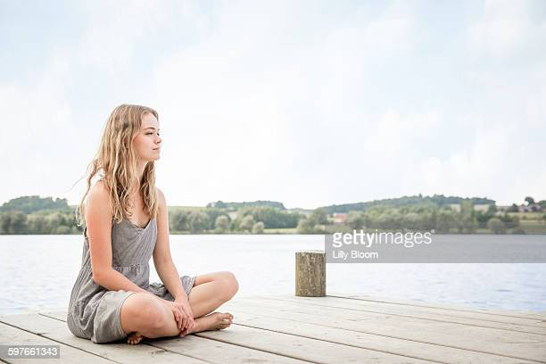 Portrait of young woman sitting on jetty, crossed legs