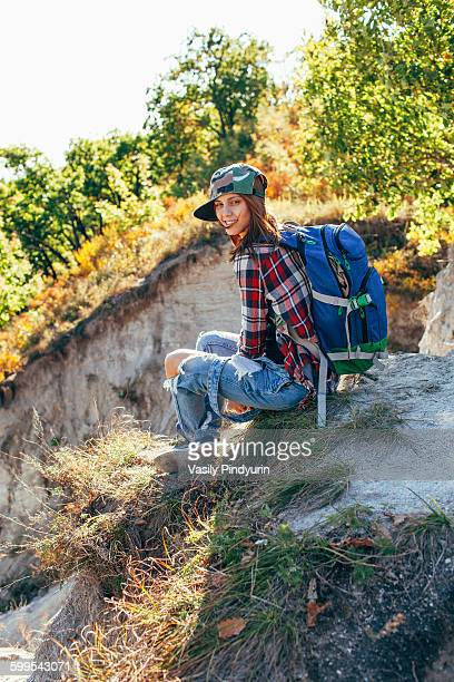 Portrait of young woman sitting on mountain