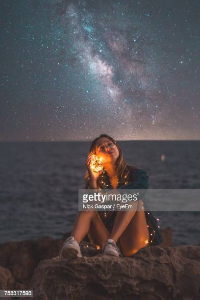 portrait of young woman sitting on rock at beach against sky at night - astronomy stock pictures, royalty-free photos & images
