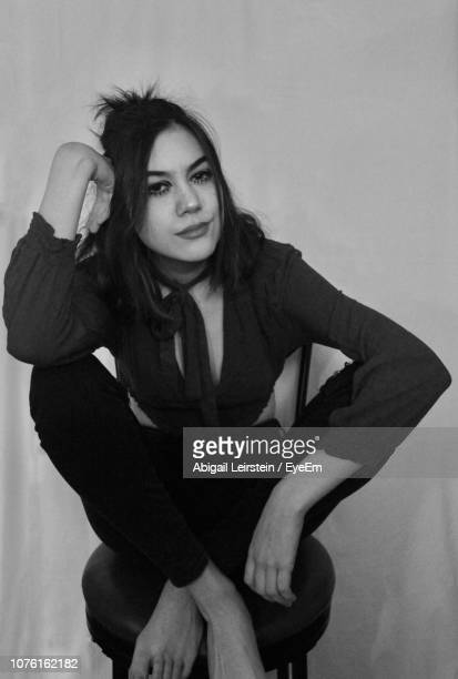 Portrait Of Young Woman Sitting On Seat Against Wall