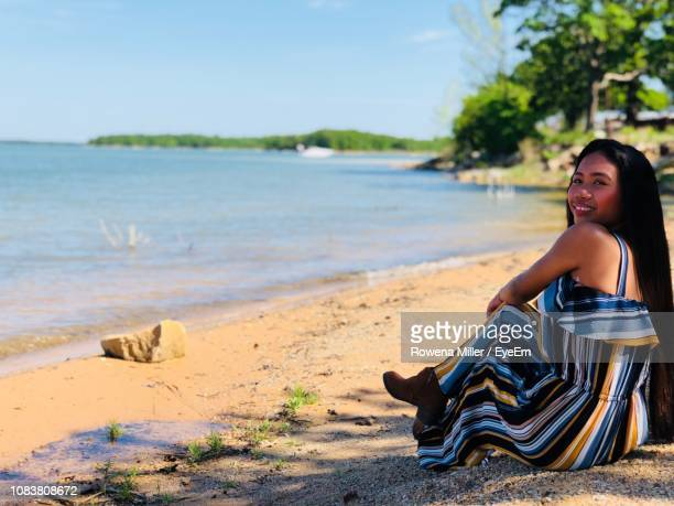 portrait of young woman sitting on shore at beach against clear sky - rowena miller stock photos and pictures