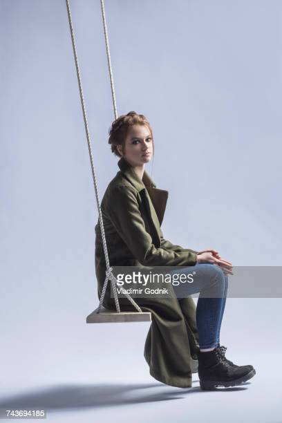 Portrait of young woman sitting on swing against purple background