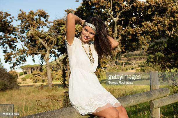 Portrait of young woman sitting on wooden fence