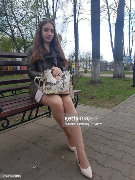 portrait of young woman sitting outdoors - mini skirt stockings stock pictures, royalty-free photos & images
