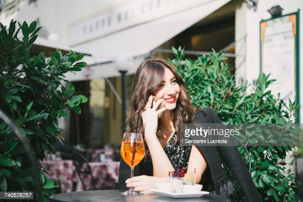 portrait of young woman, sitting outside bar, using smartphone - muro stock photos and pictures