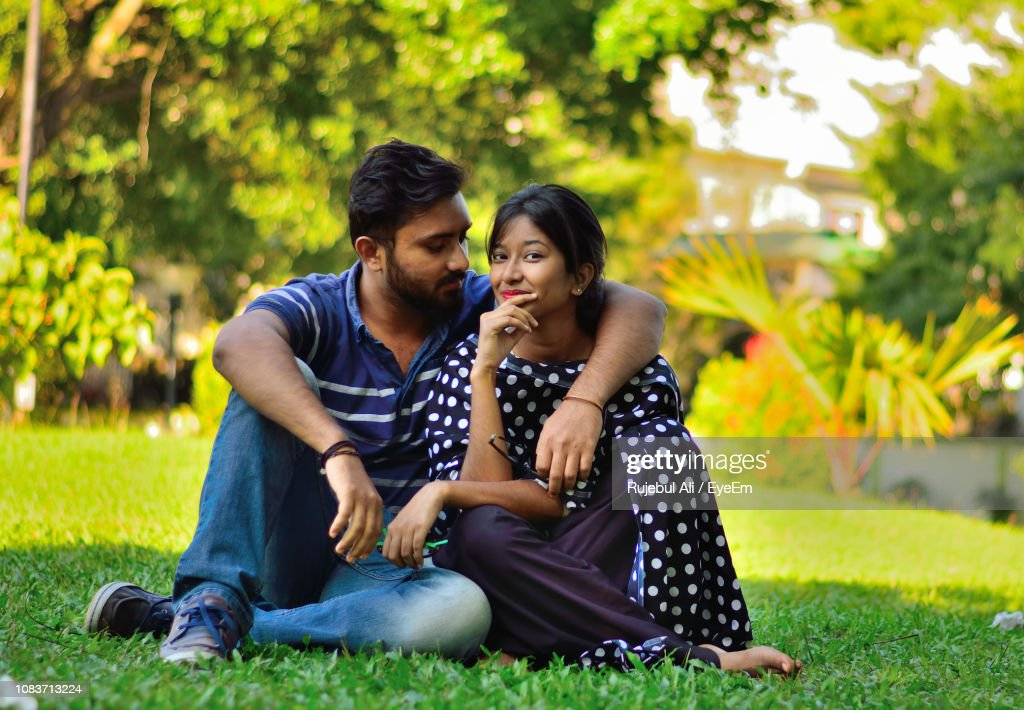 Portrait Of Young Woman Sitting With Boyfriend At Park : Stock Photo