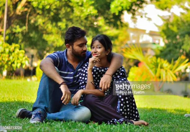 portrait of young woman sitting with boyfriend at park - guwahati stock photos and pictures