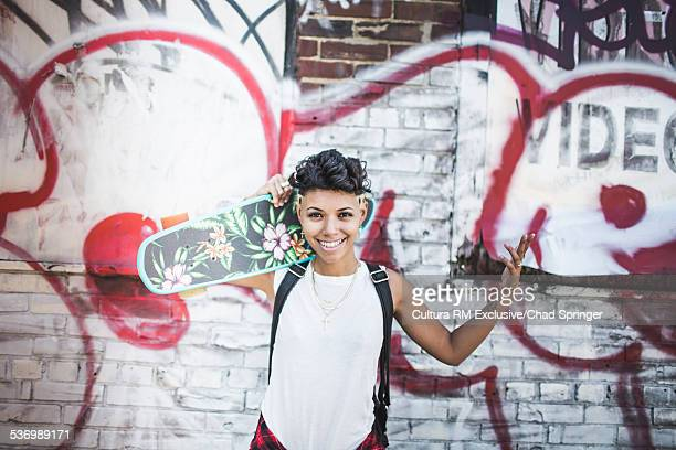 Portrait of young woman skateboarder and graffiti wall