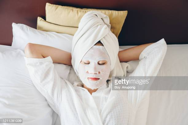 portrait of young woman sleeping on bed with applying facial mask for enhance her skin. - serene people stock pictures, royalty-free photos & images