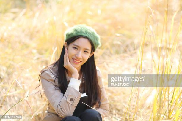 portrait of young woman smiling in autumn - ベレー帽 ストックフォトと画像