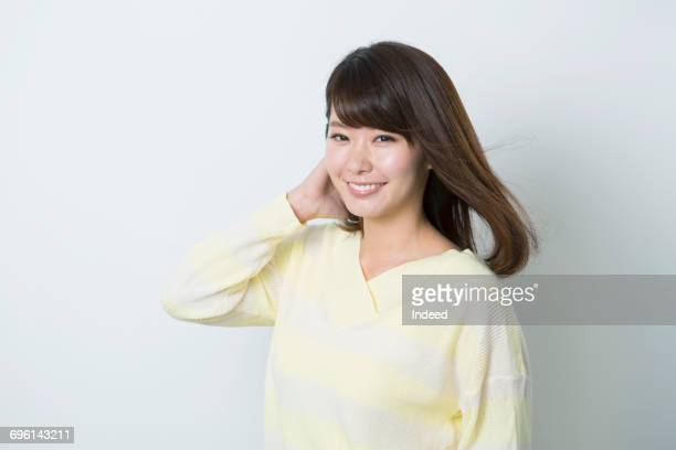 portrait of young woman, smiling - 髪に手をやる ストックフォトと画像