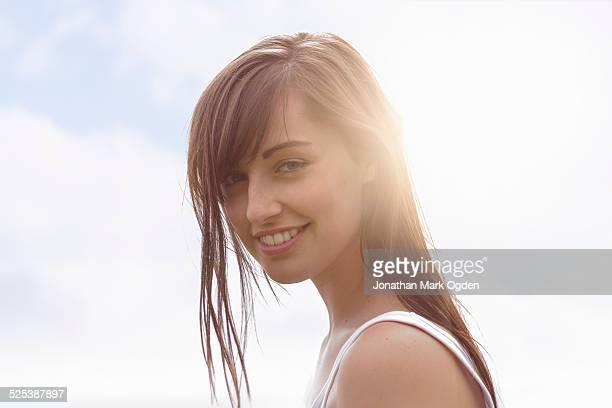 portrait of young woman smiling under bright sunlight - sexy girls stock-fotos und bilder