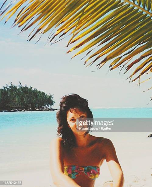portrait of young woman smiling while at beach against sky - naomi jarvis stock pictures, royalty-free photos & images