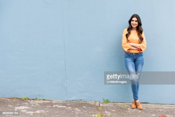 Portrait of young woman standing against a wall