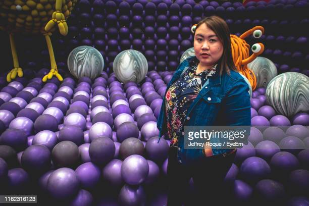 portrait of young woman standing against balls - jeffrey roque stock photos and pictures