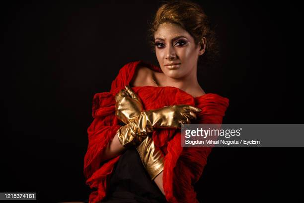 portrait of young woman standing against black background - bogdan negoita stock pictures, royalty-free photos & images