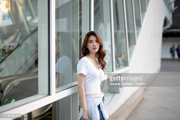 portrait of young woman standing against building - anuwat somhan stock photos and pictures